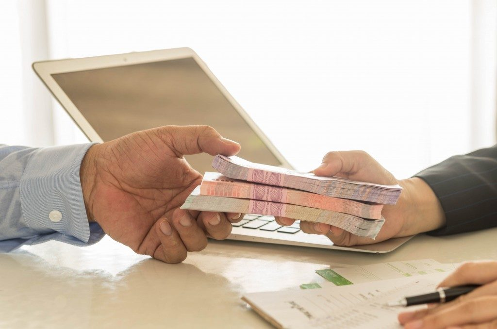 person handing a loan to the debtor