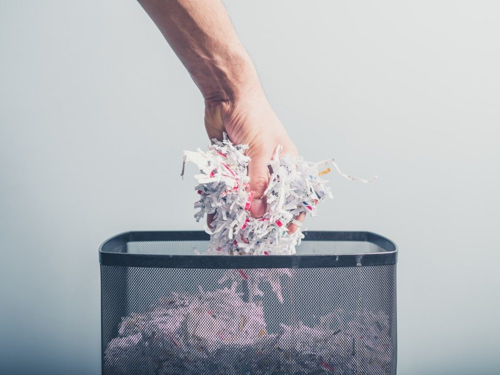 person putting shredded papers in the trash can