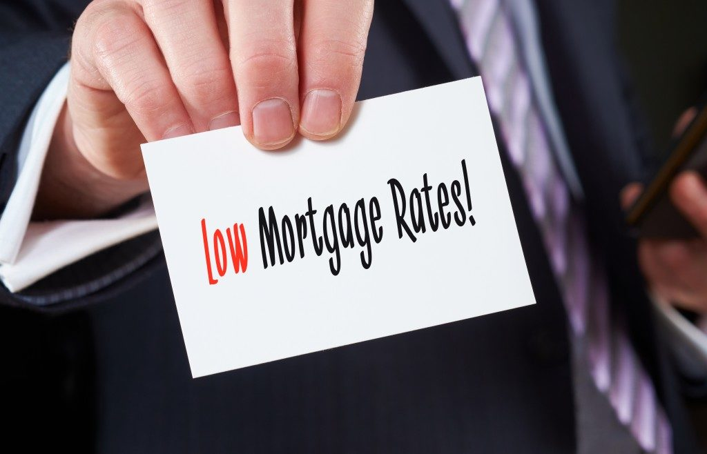 A businessman holding a business card with the words, Low Mortgage Rates, written on it.