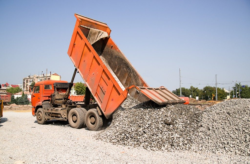 orange truck pouring over gravel