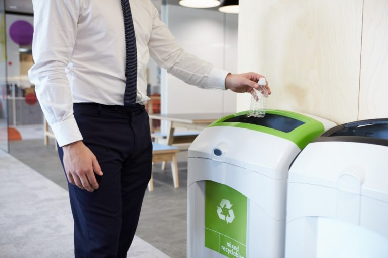 man throwing his empty bottle on a recycling bin